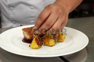 Detail of Chef Decorating Traditional Peruvian Meal Called Chicharron de Panceta de Cerdo