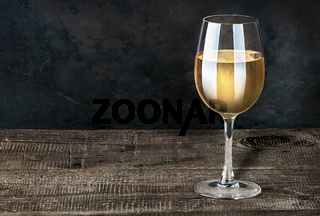 Glass of white wine on a wooden table