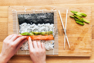 Preparing sushi. Salmon, avocado, rice and chopsticks on wooden table.