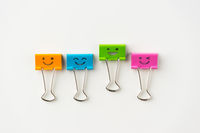 Business concept - Top view of four cute and colourful smile metal clip on white background desk for mockup