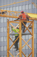 Construction workers at the top of a crane