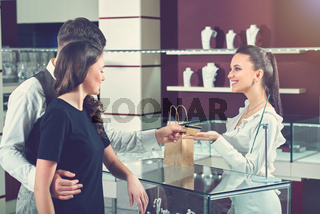 Couple paying for purchase at luxury jewelry store.