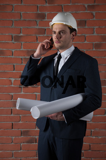 Portrait of a businessman with smartphone in white helmet on red brick wall background