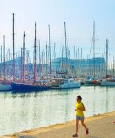 Woman running at marina. Barcelona