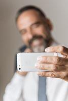 Selfie time, cheerful senior business man