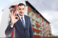 Handome real estate agent showing perfect gesture outdoors