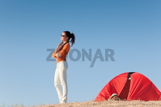 Camping happy woman outside tent on beach
