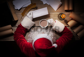 Santa Claus sitting at the table in his room and reading Christmas letter from child