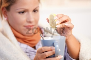 Young woman having flu drinking tea feeling bad