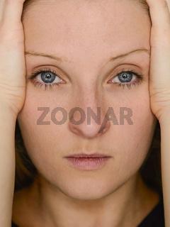 Junge blonde Frau hält Ihren Kopf zwischen den Händen