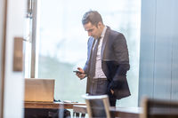 Businessman looking at smart phone in modern corporate office.