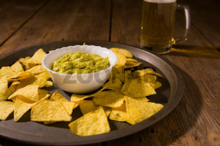 Nachos chips, salsa guacamole and beer