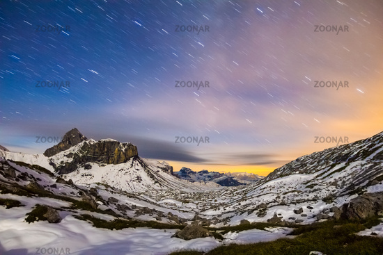 Starry night sky in snowy alpine mountains. Winter in Swiss Alps, Switzerland.