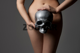 Nude woman holding silver skull cropped shot