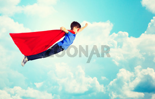 boy in red superhero cape and mask flying over sky