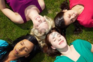Frauen liegen zusammen im Gras