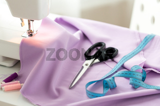 sewing machine, scissors, tape measure and fabric