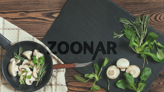 Top view of fresh mushrooms with mash salad and rosemary on a dark frying pan setting on a napkin near black stoned board on a wooden table. Copy space