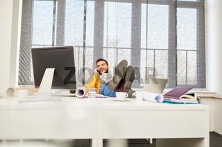 Geschäftsmann telefoniert entspannt im Büro
