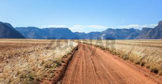 Straight desert dirt road track passes grassland towards mountains.