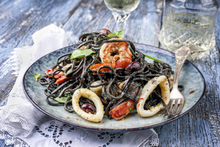 Italian linguine con tinta de calamari and prawns with olives as close-up on a plate