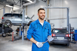 auto mechanic or smith with wrench at car workshop