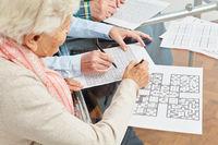 Alte Frau löst Sudoku Rätsel als Gedächtnistraining