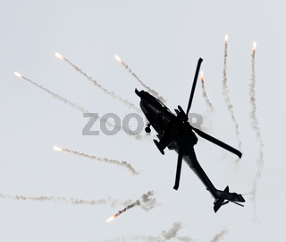 LEEUWARDEN, THE NETHERLANDS - JUN 10, 2016: Dutch AH-64 Apache attack helicopter firing off flares during the Royal Netherlands Air Force Days