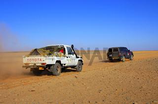 Jeeps fahren auf einer Pistenstrasse durch eine Wüstenlandschaft