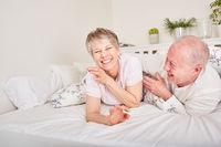 Senioren lachen ausgelassen im Schlafzimmer