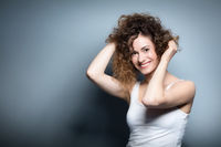Young smiling woman holding her curly hair up.