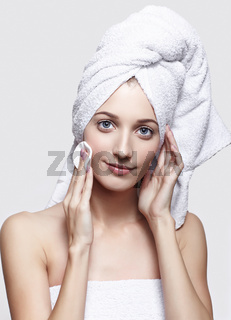 Young woman with bath towel on the head and cosmetic pad in hand