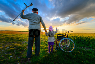 Miracle recovery: Old man gets up from wheelchair and raises hands up. Overjoyed grandfather standing up and holding hand of his granddaughter. Shot in a meadow. Recovery concept