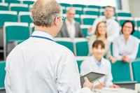 Dozent mit Tablet Computer unterrichtet Medizin