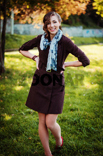 Portrait of smart cheerful girl with old-fashioned hairstyle outdoor in brown coat and shawl around her neck.