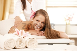 Happy young woman enjoying back massage