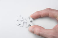 A Hand bringing two puzzle pieces together