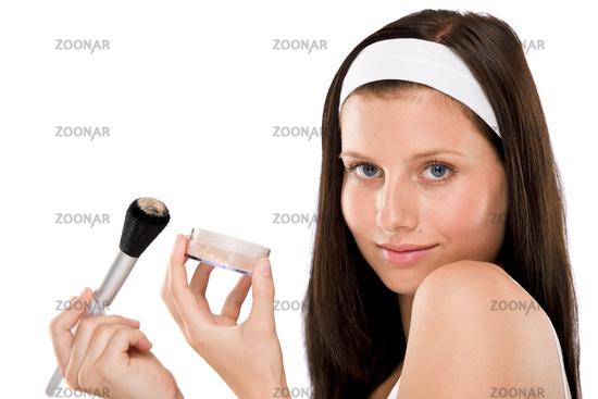 Beautiful woman applying powder with brush