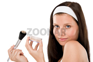 Beautiful woman applying powder with brush
