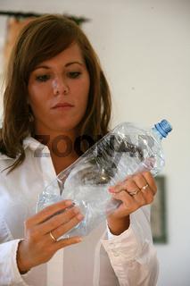 Frau zerknüllt Plastikflasche