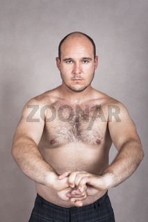 Serious shirtless man showing his strong body