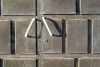 Pair of white metal handles on a brown garage door with a keyhole.