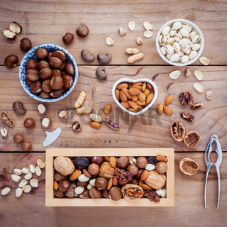 Different kinds of nuts walnuts kernels ,macadamia,hazel nuts, almond,chest nuts,cashew nuts and pistachio with nut and shell crackers on rustic wooden background.
