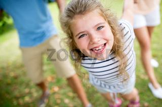 Lachendes Mädchen spielt mit Eltern