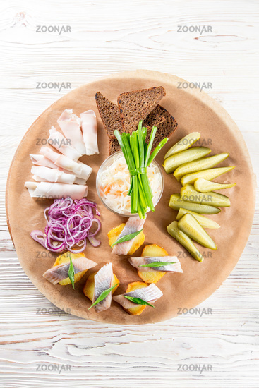 Sandwiches of potato slices with herring, red onions, herbs and rye bread. bacon slices and pickles