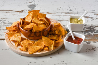 Nachos in an earthenware bowl and sauces