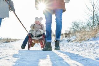 Eltern ziehen Schlitten mit Kind durch den Schnee