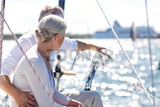 happy senior couple on sail boat or yacht in sea