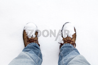 Human legs standing in the snow.