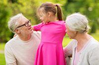 senior grandparents and granddaughter at park